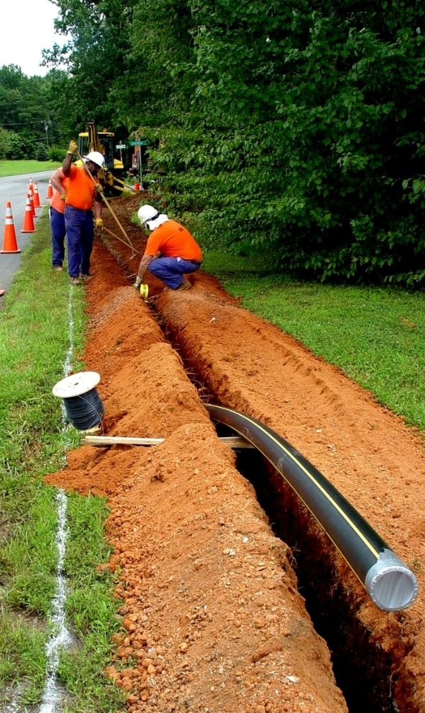 Utilities crew installing a new gas main line on the street