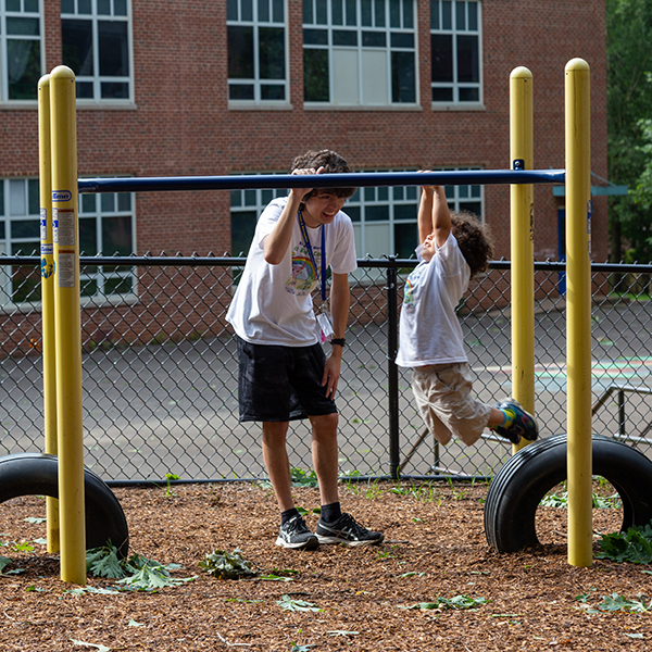 Buddy camp counselor and child playing on playground